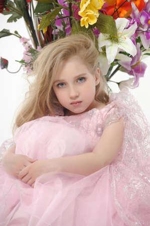 la ni�a en un vestido rosa con un ramo de flores photo