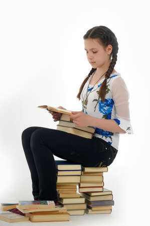 School Girl Sitting On The Stack Of Books photo