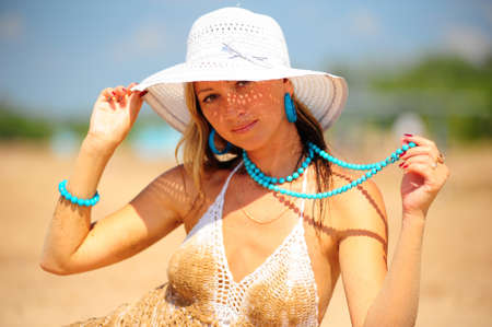 girl on the beach in a white dress and hat photo