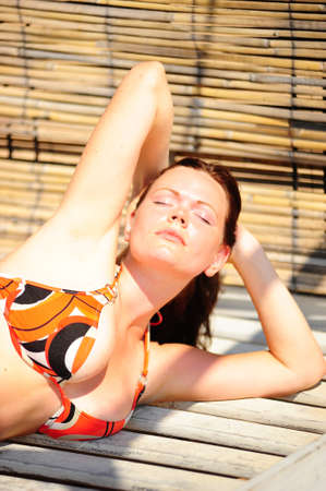 young woman sunbathes photo