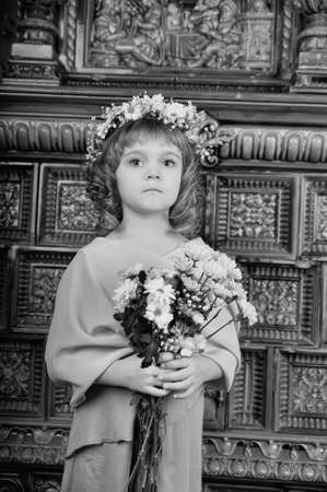little girl with a wreath of flowers and bouquets photo