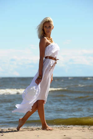 Girl in white dress on beach photo