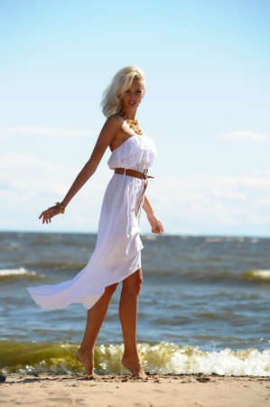 Girl in white dress on beach photo