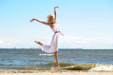 mouettes: Jeune fille en robe blanche sur la plage