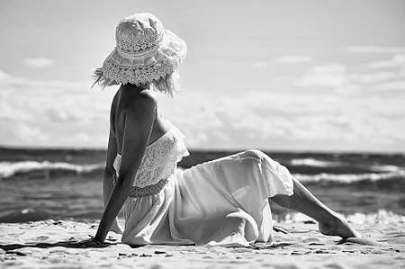 the girl in a dress and hat on the beach Stock Photo - 14552298