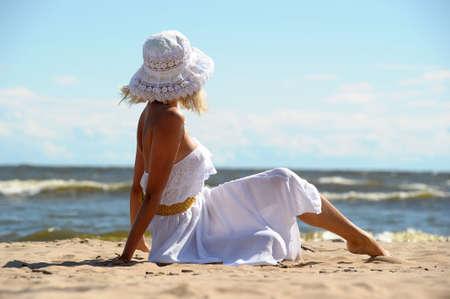 Девушка в платье и шляпе на пляже