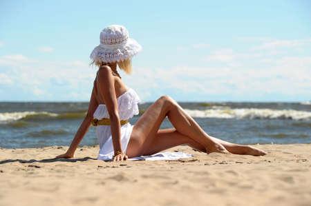 la niña en un vestido y un sombrero en la playa Foto de archivo
