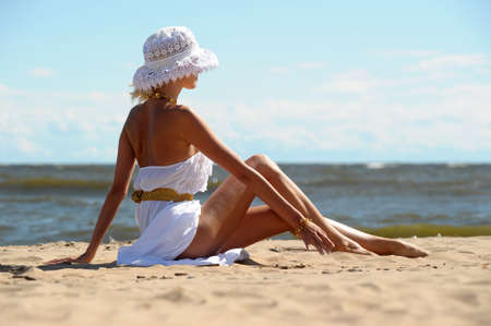 das Mädchen in einem Kleid und Hut am Strand