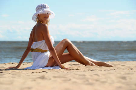 the girl in a dress and hat on the beach photo