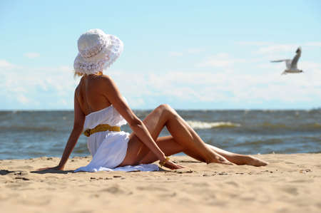 the girl in a dress and hat on the beach Stock Photo - 14552251