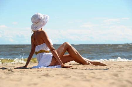 the girl in a dress and hat on the beach Stock Photo - 14552277