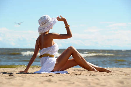 the girl in a dress and hat on the beach Stock Photo - 14577766