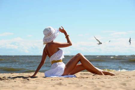 mujer ba�andose: la ni�a en un vestido y un sombrero en la playa Foto de archivo