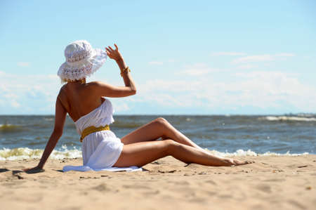the girl in a dress and hat on the beach Stock Photo - 14577763