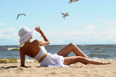 the girl in a dress and hat on the beach Stock Photo - 14577583