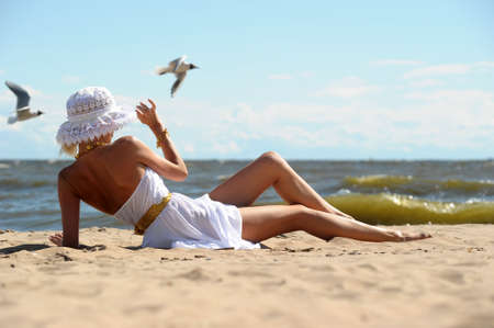 the girl in a dress and hat on the beach Stock Photo - 14577587