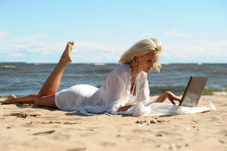 Happy blonde woman at a beach with a laptop Stock Photo - 14577551