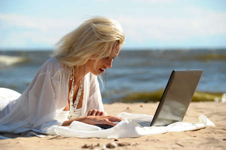 Happy blonde woman at a beach with a laptop Stock Photo - 14577538