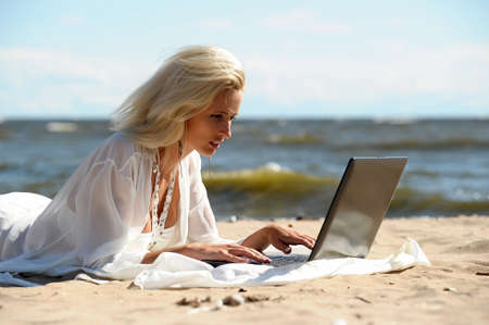 Happy blonde woman at a beach with a laptop Stock Photo - 14577537