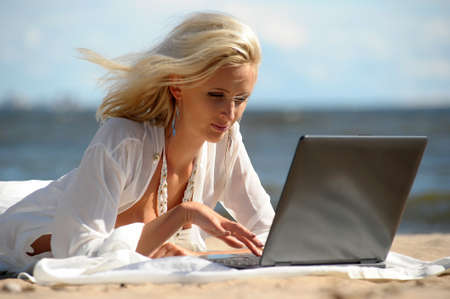 Happy blonde woman at a beach with a laptop Stock Photo