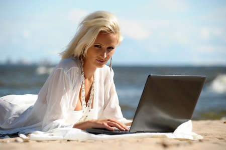 Happy blonde woman at a beach with a laptop Stock Photo - 14577533