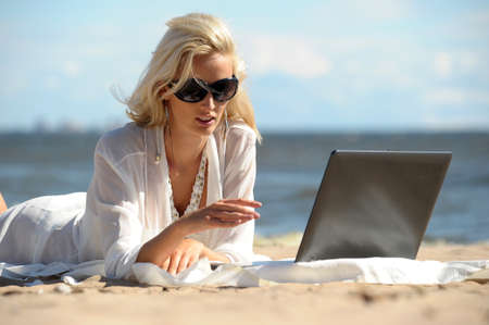 Happy blonde woman at a beach with a laptop Stock Photo - 14577548
