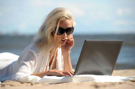 Happy blonde woman at a beach with a laptop Stock Photo - 14577554
