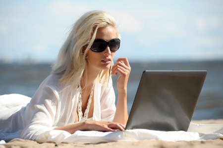 Happy blonde woman at a beach with a laptop Stock Photo - 14577534