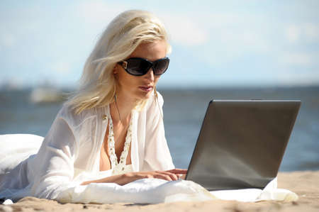 Happy blonde woman at a beach with a laptop photo