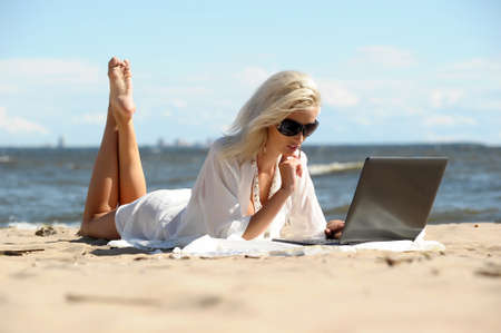 Young woman in bikini with laptop, working, chatting, searching or walking in internet on beach photo