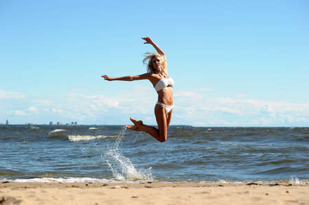 Young beautiful girl doing gymnastic jumps outdoors photo