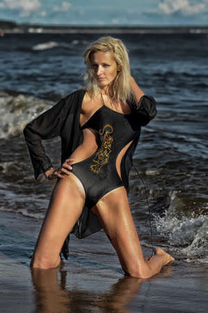 Beautiful blonde woman in black swimwear photo