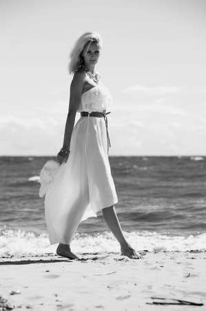 along: the girl in a dress and hat on the beach, black and white