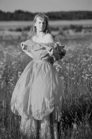 young woman in an old dress in the middle of the field Stock Photo