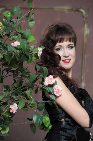 young woman in elegant dress next to a bush of roses photo
