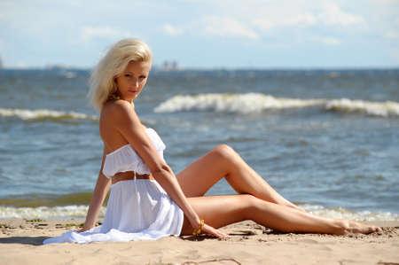 position love: femme en robe blanche assis sur la plage