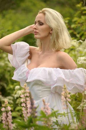 Girl in a white dress walks in field photo