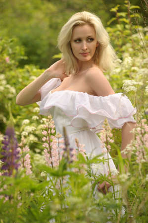 Girl in a white dress walks in field photo