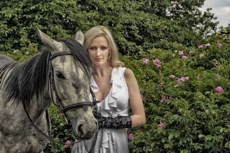 blonde with a horse among the bushes of a blooming rose hips photo