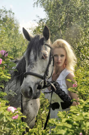 blonde with a horse among the bushes of a blooming rose hips Stock Photo - 14907485