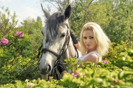 beautiful young woman holding a horse by the reins photo
