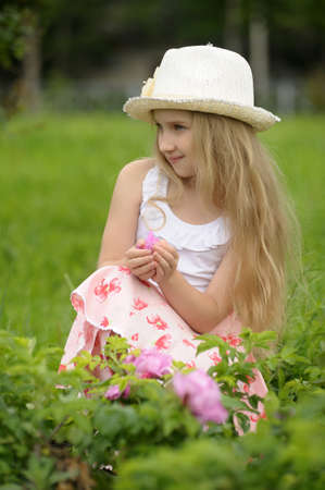grass skirt: little long-haired blonde in a white hat in the park