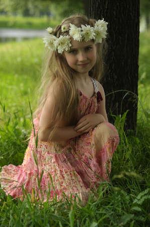 kleines Mädchen in einem Kranz aus weißen Blüten