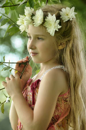 little girl in a wreath of white flowers photo