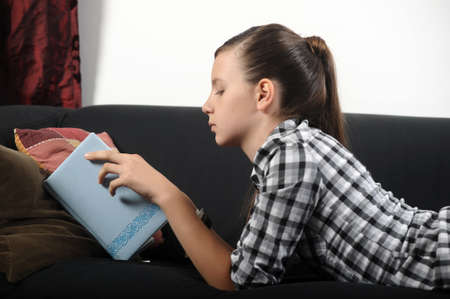 Pretty young girl reading book on sofa  photo
