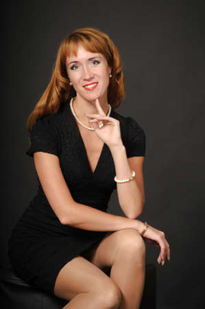 Portrait of red-haired girl in a black dress photo