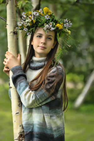 Teen girl with a wreath of flowers on her head photo