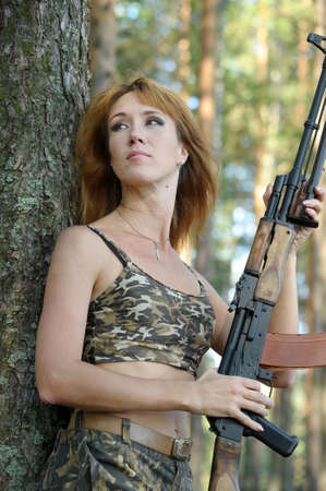 camouflage woman: Armed beautiful young woman