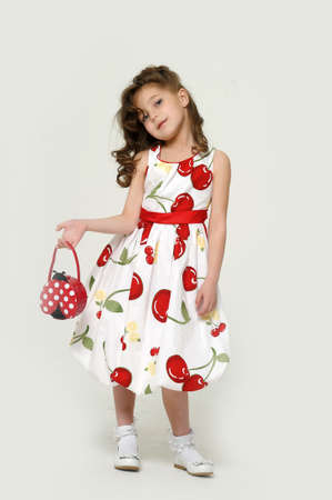 girl in a white dress with flowers with a bag in his hand photo