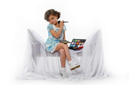 Little girl trying makeup isolated on white background photo